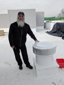 Martin Kolt Standing Next To The Aura Vent With A Curb Mount Flange - Installed On A Wooden Roof Curb